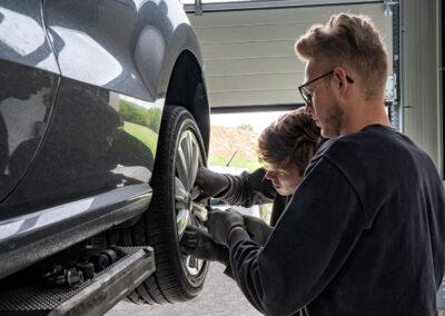 Werkstatt-Mitarbeiter bei der Montage eines Rades an einem Fahrzeug