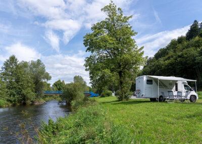 Wohnmobil mit Markise und Campingstühlen auf einem Stellplatz an der Ruhr