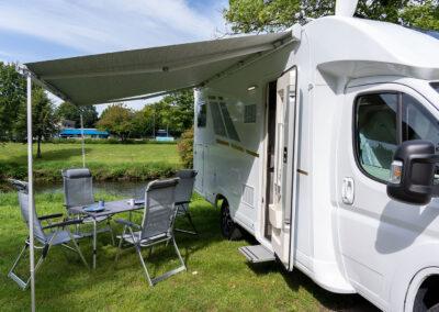 Wohnmobil mit Markise und Campingstühlen